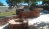 Falcon landscapes outdoor kitchen with raised bar, firepit, bench seating and travertine paver patio